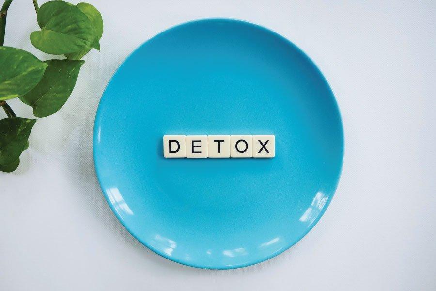 Een blauw bord met daarop de letters detox, het engelse woord voor ontgiften, met in de linkerbovenhoek een plant.