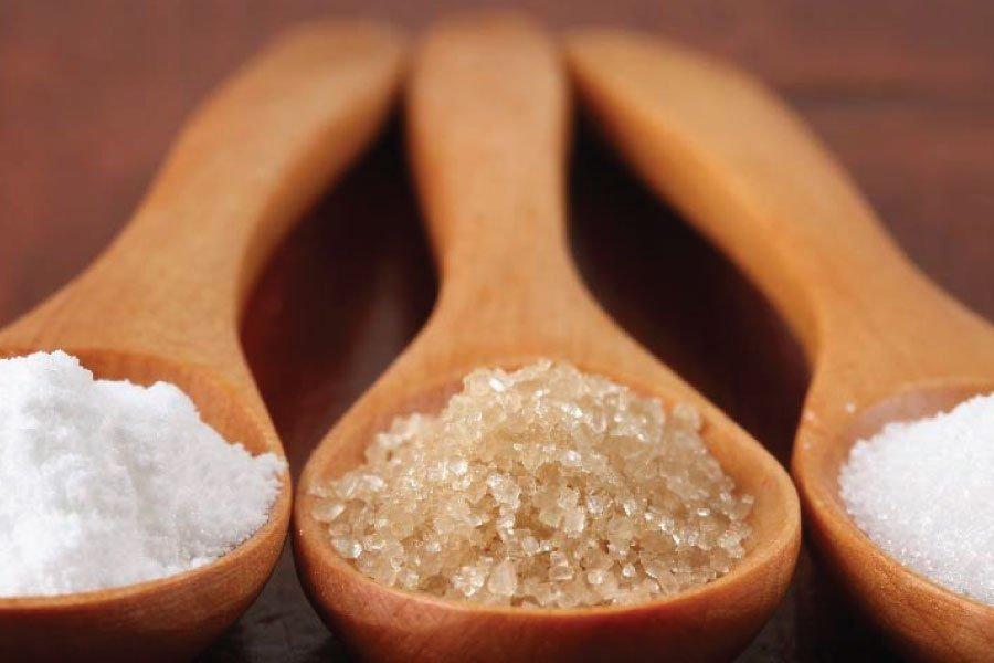 Drie houten lepels met daarop drie verschillende soorten suiker die als basis voor kefir gebruikt kunnen worden: poedersuiker, bastardsuiker en kristalsuiker.