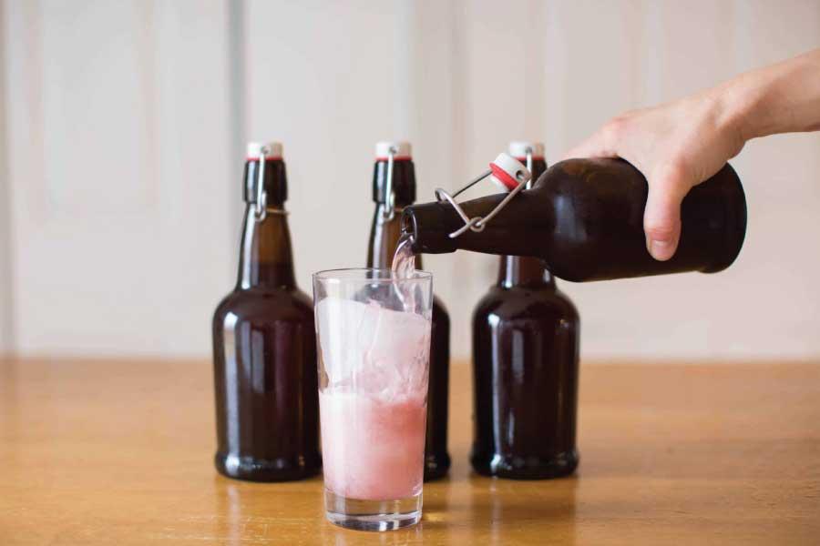 Een glas wordt gevuld met huisgemaakte waterkefir dat geschonken worden vanuit bruine beugelflessen.