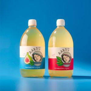 De twee literflessen van Aard'g naast elkaar: Waterkefir Original en Kombucha Original. Op een blauwe achtergrond.