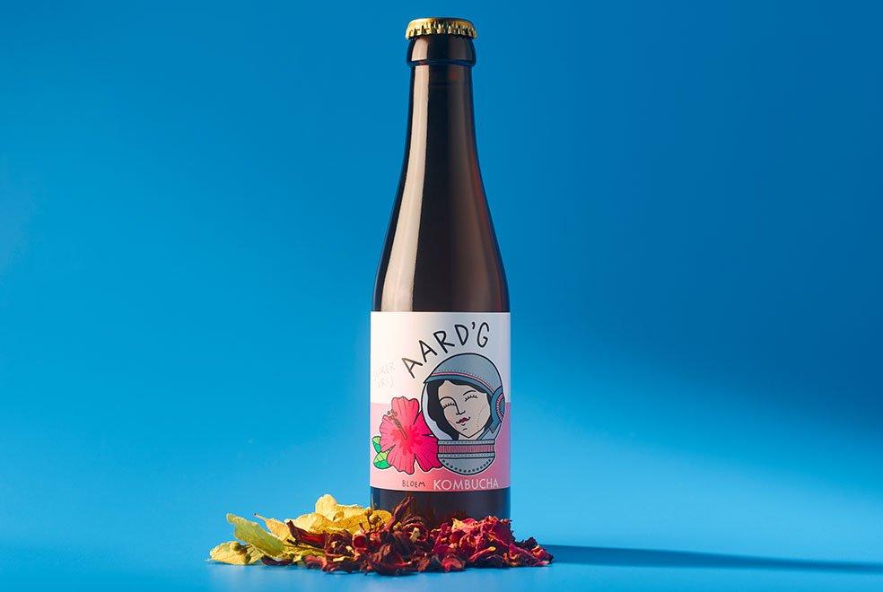 Een fles Aard'g Bloem Kombucha op een blauwe achtergrond met de ingrediënten hibiscus, linde en rozenbottel ernaast.
