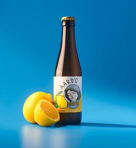Een fles Aard'g Citroen Kombucha op een blauwe achtergrond met de ingrediënten citroen ernaast.