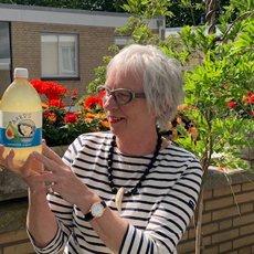Een klant van Aard'g, Adewij, met een fles Aard'g Waterkefir Original in haar hand.