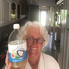 Een klant van Aard'g, Carla, met een fles Aard'g Waterkefir Original in haar hand.