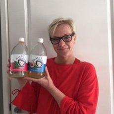 Een klant van Aard'g, Eugenie, met een fles Aard'g Kombucha en Waterkefir Original in haar hand.