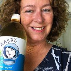 Een klant van Aard'g, Hennie, met een fles Aard'g Waterkefir Original in haar hand.