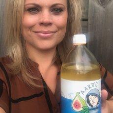 Een klant van Aard'g, Sylvia, met een fles Aard'g Waterkefir Original in haar hand.