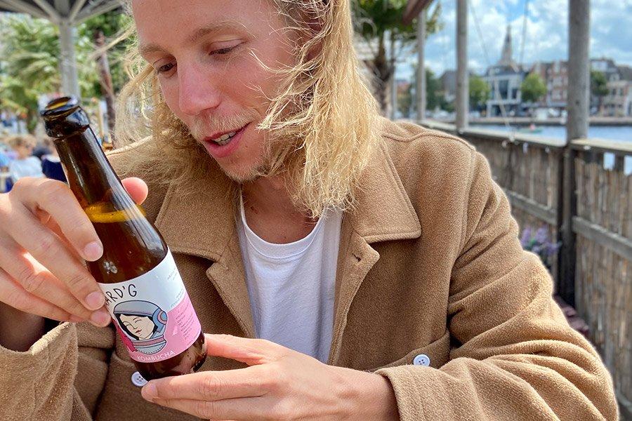 Een van de oprichters van Aard'g, Max, die een flesje Aard'g Bloem Kombucha bekijkt.