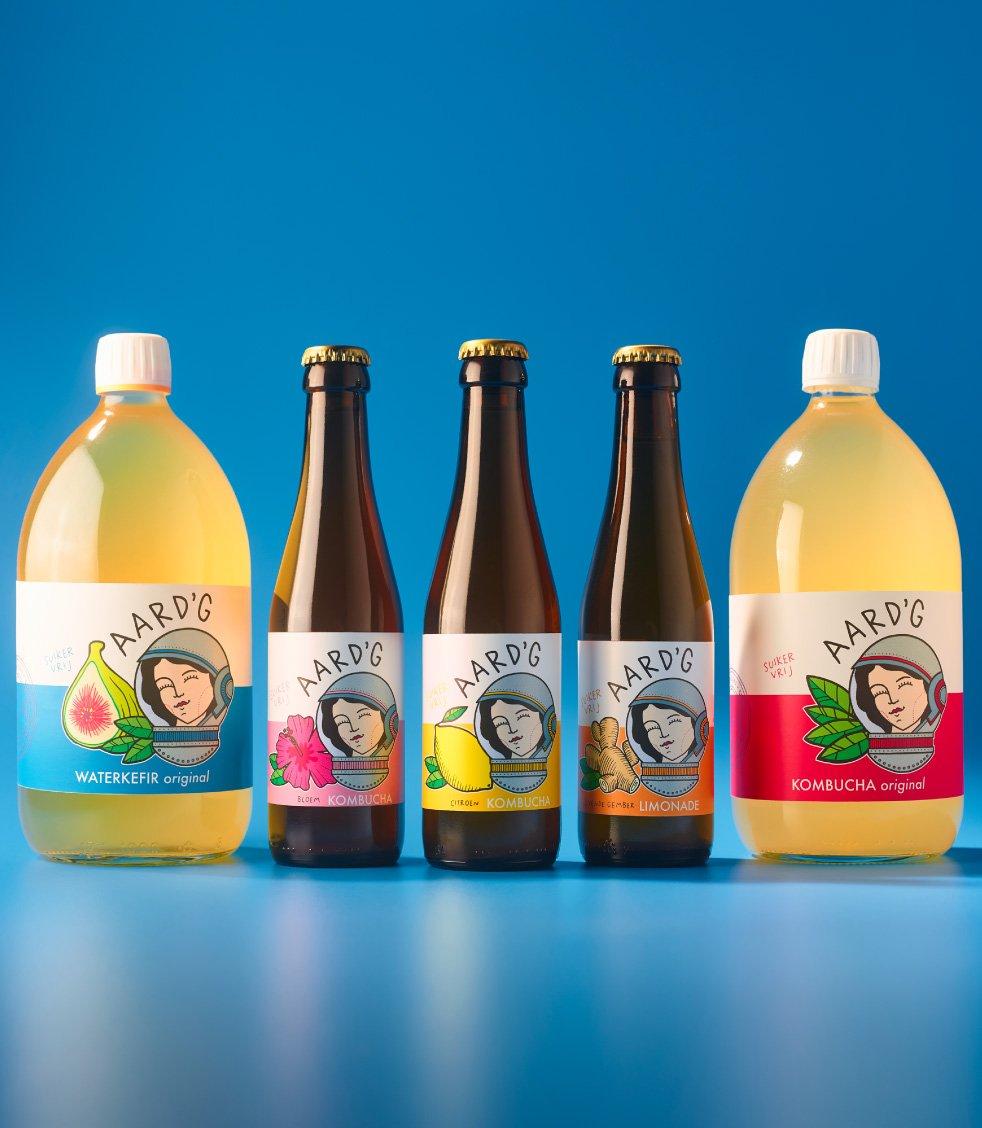 Alle producten van Aard'g op een rij: Waterkefir Original, Bloem Kombucha, Citroen Kombucha, Levende Gember Limonade en Kombucha Original. Op een blauwe achtergrond.