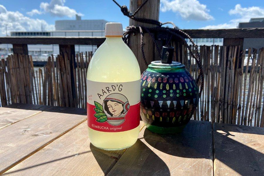 Een fles Aard'g Kombucha Original naast een oliebrander op een houten tafel.