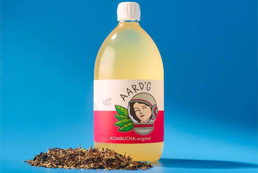 Een fles Aard'g Kombucha Original op een blauwe achtergrond met de ingrediënten groene thee ernaast.
