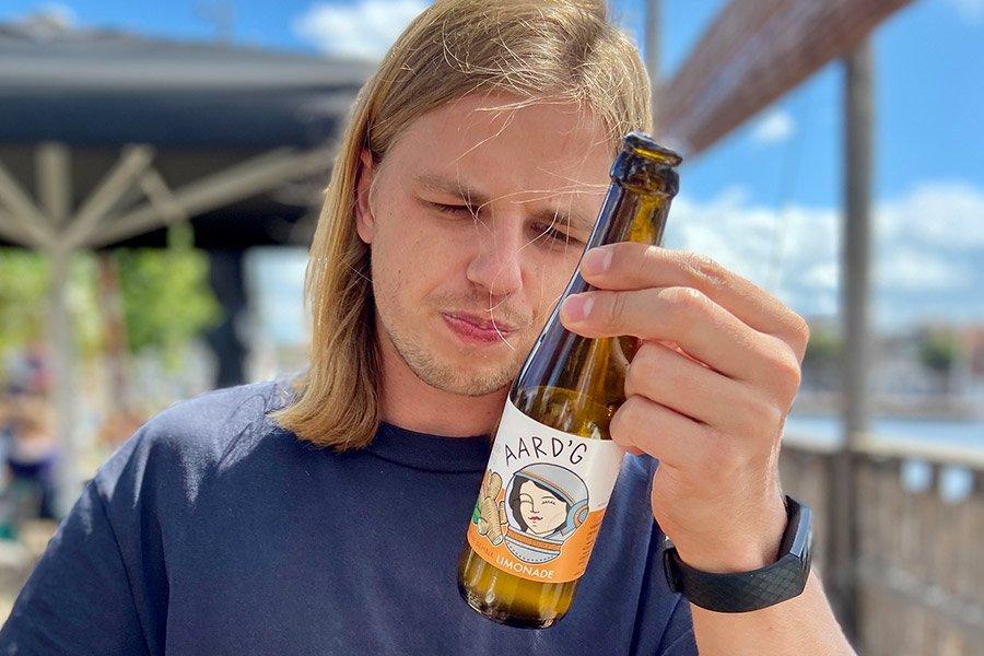 Een van de oprichters van Aard'g, Zeger, die een flesje Aard'g Levende Gember Limonade bekijkt.
