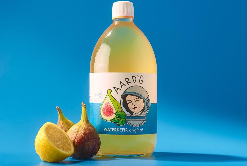 Een fles Aard'g Waterkefir Original met de ingrediënten vijg en citroen op een blauwe achtergrond.