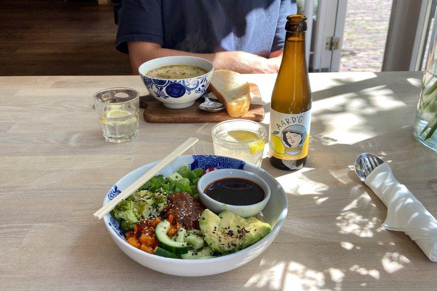Een fles Aard'g Citroen Kombucha op een tafel met daarnaast een maaltijdsalade en kom soep.