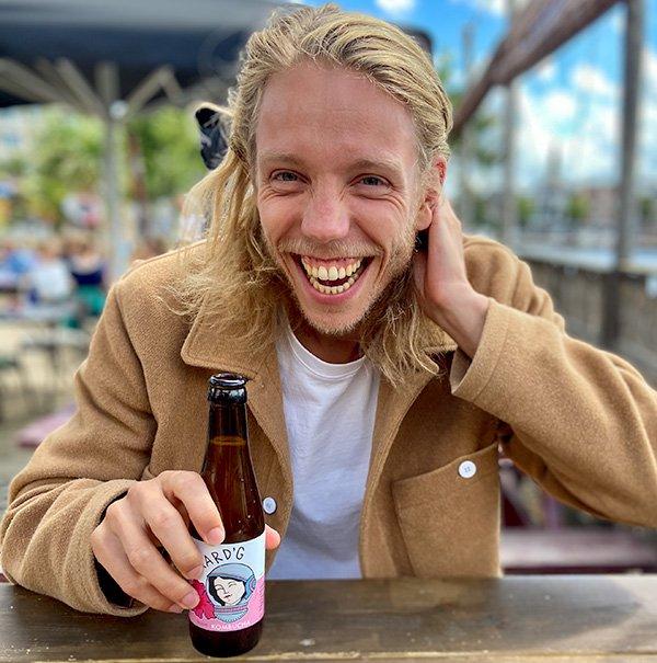 Max, mede-oprichter van Aard'g,  met een fles Bloem Kombucha