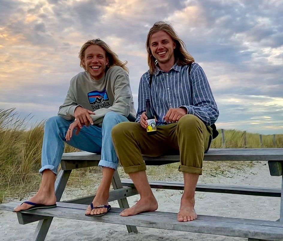 Max en Zeger, de oprichters van Aard'g, zitten op een bankje op het strand
