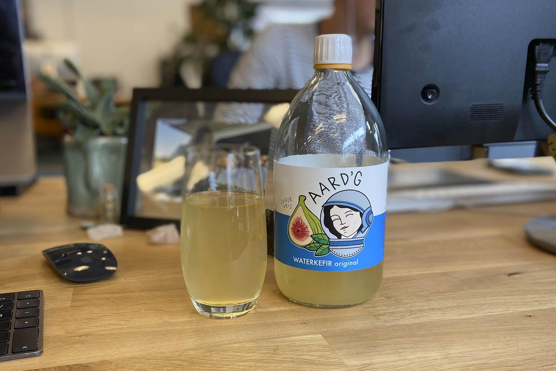 Een fles en glas Aard'g Waterkefir Original op een bureau met op de achtergrond een foto, laptop en monitor.