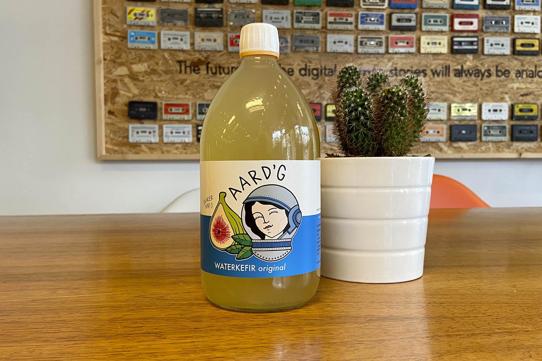Een fles Aard'g Waterkefir Original naast een cactus op een houten tafel.