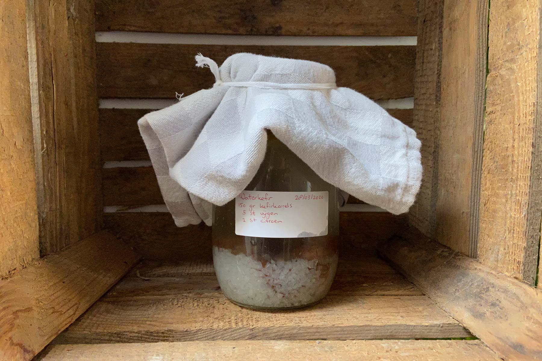 Een pot zelfgemaakte waterkefir in een hout kistje.