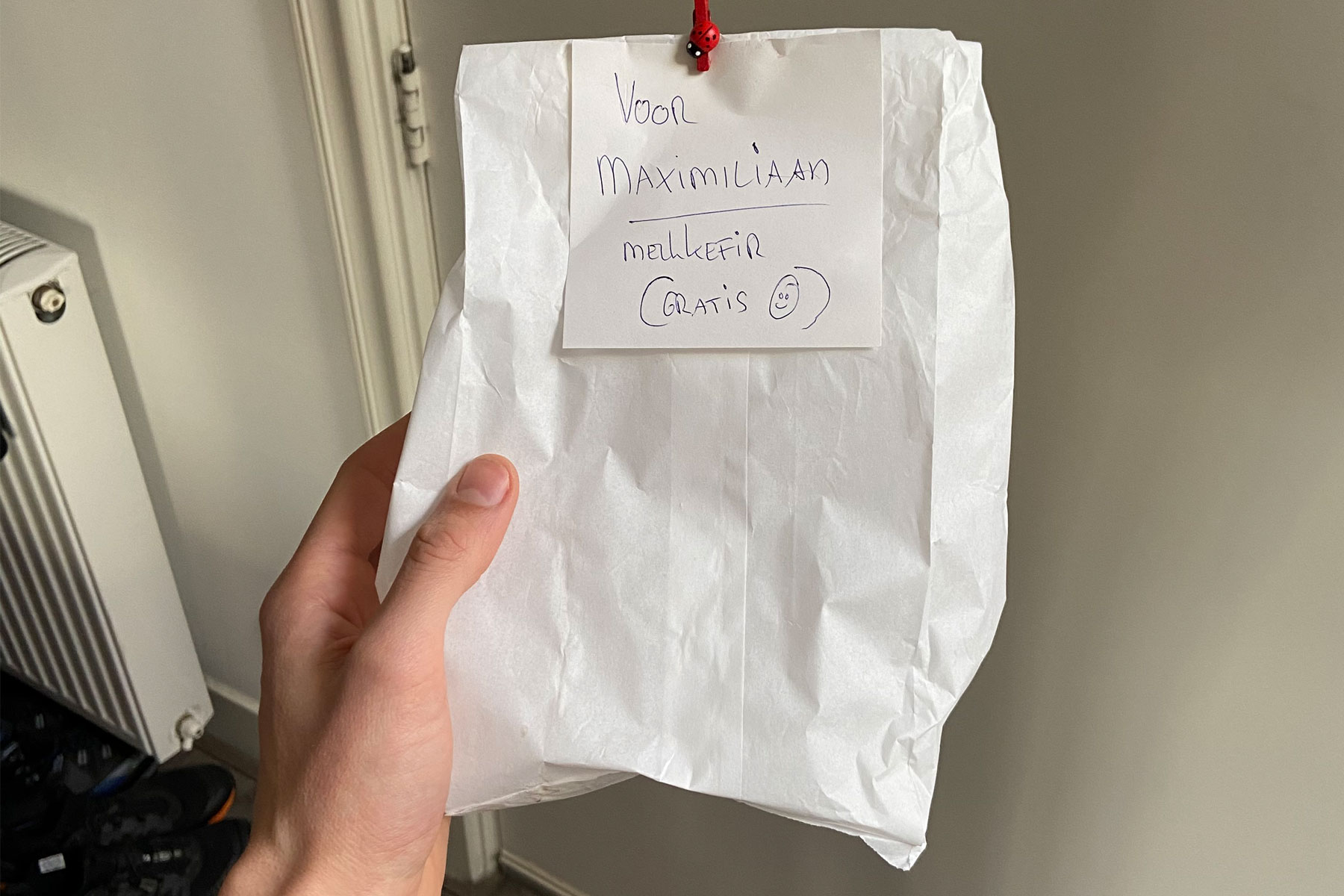 Een papierenzakje met daarop de tekst: voor Maximiliaan, melkkefir gratis. In de hand vastgehouden.