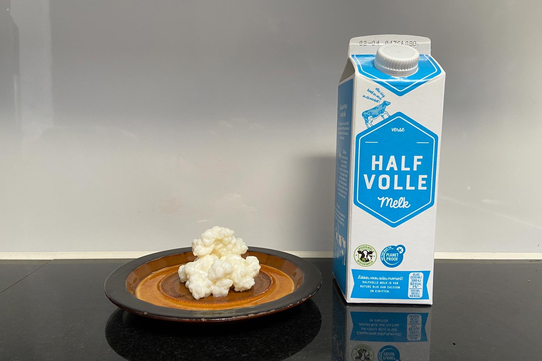 Melkkefirkorrels op een bruine schaaltje naast een flesje halfvolle melk.